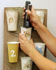 4. Schreiben Sie nun mit einem Goldstift die Zahlen 1 bis 24 auf die Becher (bei den Bechern mit den Sternen auf den Stern).  5. Verteilen Sie die Becher probehalber auf dem liegenden Brett, bis es gut aussieht und tackern Sie sie dann nacheinander fest (sollten Sie keinen Tacker haben, können Sie auch kleine Nägel verwenden).  6. Schlagen Sie jetzt noch die Geschenke in Seiden- oder Packpapier ein und verteilen Sie sie auf die Becher.  7. Lehnen Sie den Adventskalender an eine freie Wand.