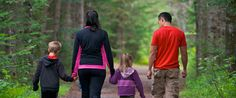 La Mauricie National park-Two grown-ups and two children walking hand in hand along a trail.