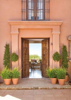 Entrada a la casa con fachada color teja. Desde la entrada