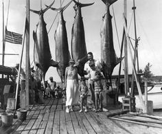 American author Ernest Hemingway with Pauline, Gregory, John, and Patrick Hemingway and four marlins on the dock in Bimini, 20 July 1935.