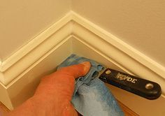 Removing excess caulk with wet paper towel wrapped around putty knife.