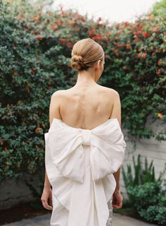 Tight bun and a bow dress: http://www.stylemepretty.com/2013/07/31/unique-wedding-fashion-trends/   Photography: Chudleigh - http://www.chudleighweddings.com/