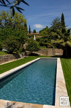 Piscine forme bassin de nage traditionnel | Piscinelle.La margelle en pierre naturelle et la couleur de l'eau donnent un aspect bassin traditionnel à cette piscine contemporaine.