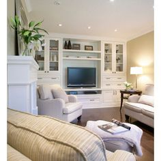cozy family room- wood floors, recessed lights, a wall of creamy-white built in cabinets.