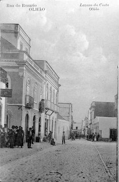 A Rua do Comércio já se chamou Rua do Rosário, mas os olhanenses sempre se lhe referiram como Rua das Lojas.  Nasceu com um traçado estreito que ligava os bairros ribeirinhos ao largo da Igreja Matriz e foi, desde sempre, um eixo urbano da maior importância não só por acolher a maior parte da vida comercial como também por alojar as instituições públicas que foram sendo criadas na vila. Testemunha da sua importância é o facto de ter sido a primeira rua a ser calcetada em 1838. Algarve, Portugal, Old Photos, Street View, Photography, Cubist Architecture, The Neighborhood, Cities, Fotografia