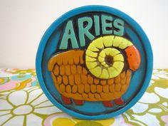 Vintage 1960s Retro Groovy Aries Zodiac Sign MOD R. Dakin 1969 Japan Coin Piggy Bank  Description: Vintage, circa 1960s - 1970s, paper mache plaster aqua blue Zodiac sign - Aries - piggy bank - with painted ram on the front and back and imprinted - R. Dakin & Company 1969 Made In Japan. Measures 4.50 wide and 4.50 high and 3 thick. Groovy Good condition with some nicks around the coin drop slot and some wear from age/use. We have several retro banks - then check my other items. Era: ...
