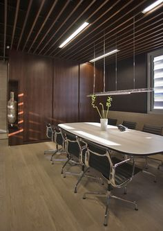 Eames aluminum group chairs and Eames segmented base table in a modern office setting.