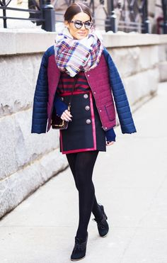Camila Coelho in a two-tone puffer jacket, striped top, and mini skirt