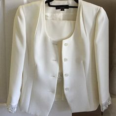 NWT Tahari skirt suit New with tags off white suit jacket and skirt 2 piece. Tahari Arthur S. Levine Luxe line. Beautiful lace and floral detailing on suit jacket and skirt hem. Buttons on the jacket also have crystal detailing. Tahari Skirts