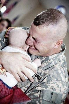 A soldier meets his baby for the first time.