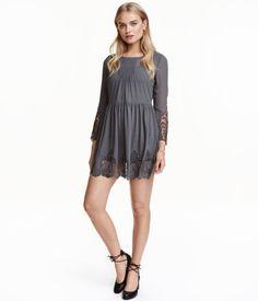 Donkergrijs. Een korte jurk van chiffon met kant onder aan de mouwen en de rok. De jurk heeft driekwart trompetmouwen, platte plooitjes boven, een splitje