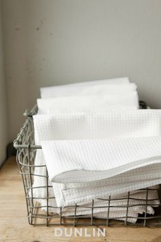 Need some wire baskets in the kitchen with towels or oils/spices...black cabinets, wire baskets, white washed wood, gray/white stripe linens