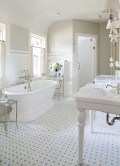 Beautiful vintage style bathroom shows house can have a vintage style and still have all the luxury elements you want. Love the white tile floors with grey pegs (very similar to the original bathroom tile in the 1930s brick colonial I grew up in), and the subway tile two-thirds of the way up the wall. Lovely sconces, sink consoles, side tables by the tub, and color. Sign me