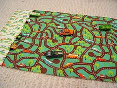 Car roll-up Play Mat. I don't know if I'd use that busy fabric. I might, instead, use a plain fabric and applique more simple (and larger) roads, trees, etc. and, make it place mat sized, with pockets for only two cars.