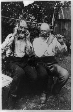 Appalachian man playing flute while another man covers his ears, ca. 1914.