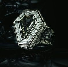 Pallbearer ring - including a 6.81ct fancy dark grey shield cut diamond which hinges open to reveal a hidden cross composed of black princess cut diamonds