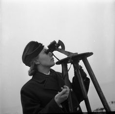 GIRL GUNNERS: THE WORK OF THE AUXILIARY TERRITORIAL SERVICE AT AN EXPERIMENTAL STATION, SHOEBURYNESS, ESSEX, ENGLAND, 1943. 23 year old ATS Junior-Commander Joyce Bathurst looks through binoculars as she times anti-aircraft shells with a stop watch from the moment of firing until the burst. She shouts the results out to a colleague who records the information.