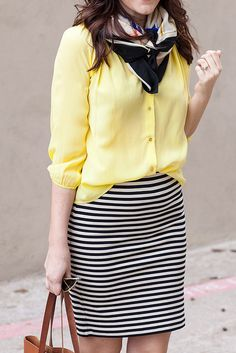 Style a black & white striped skirt with a pale yellow blouse and a black & color printed scarf
