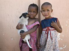 """Susan (age 7) holds a dog outside the community home where she lives, in Omaheke Region. She stands with her friend, an indigenous San who also lives at the home. Their caregiver, Nora, fosters 13 children. Nora began this work six years ago. """"I would go through the community and found many children living without parents - many orphaned by AIDS"""". The HIV/AIDS pandemic has reversed many social gains in Namibia. - September 2008 © UNICEF/John Isaac - http://www.unicef.org/photog"""