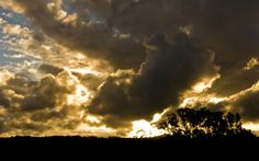 Light; Stormy - The intense light from the sun creates a stormy attitude from behind the dark clouds