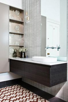 A limited palette of whites and greys and dark wood tones is spiced up with rich colour underfo...
