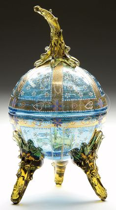 Moser Covered Bonbon Bowl, Having Blue Glass Body With White And Yellow Enameled Flowers And Gilded Bands, Finished With Three Applied Amber Glass Feet And The Bonbon Is Topped With A Matching Domed lid With Applied Ambre Glass Finial  -  James D. Julia, Inc. Auctioneers
