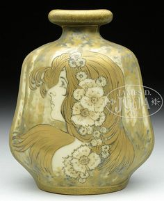 """Amphora pottery vase is decorated with the portrait of an Art Nouveau maiden with gilded hair and a flowing spray of flowers in her hair. Portrait has trees in the background and the back of the vase is decorated with painted and gilded trees. Signed on the underside """"Amphora Turn"""" as well as """"Turn Teplitz Bohemia"""" and impressed """"Amphora 575 21"""". SIZE: 5-3/4"""" t. - by James D. Julia"""
