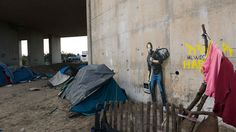 Street artist Banksy has unveiled his latest artwork, sprayed on the wall of the Calais refugee camp, depicting Steve Jobs as a refugee with his belongings slung over his shoulder, carrying an old Mac computer.