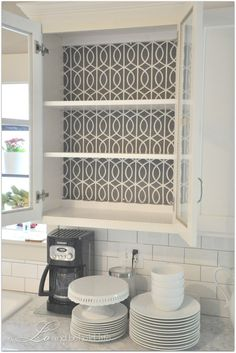 Use fabric for the backing of shelves instead of paint or wallpaper. Love this idea for glass front cabinets. Smart!
