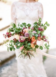 Peach and purple wedding bouquet with berries. Claire Pettibone dress.