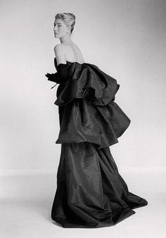 1956  A poised lady shows us her taffeta evening gown designed by Christian Dior