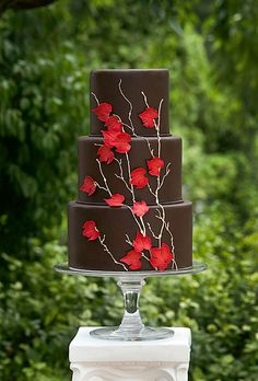 Brides.com: 22 Wedding Cakes for Dark, Modern Color Palettes. A Three-Tier Brown Wedding Cake with Red Leaves. This chocolate fondant AP Signature Cakes creation gets a fall wedding-worthy touch from the gold piped branches and red sugar maple leaves. Modern, elegant, gorgeous. See more fall wedding cakes.
