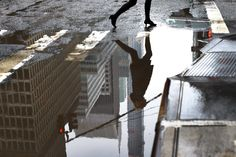 A woman walks around a puddle on Park Avenue in New York as warming temperatures started to melt snow and ice.