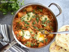 A fast tomato curry sauce takes simple boiled potatoes to the next level! Curried Potatoes with Poached Eggs - BudgetBytes.com #vegetarian #curry