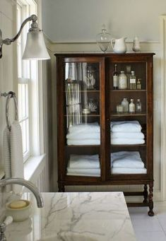 Using Vintage Furniture in your Bathrooms. It is a great option for all the Bathroom Storage Needs we have. Love the Contrast between this White Bathroom and then the Deep Wood Vintage Storage Furniture Piece. - Home Design Bad Inspiration, Bathroom Inspiration, Bathroom Ideas, Bathroom Trends, Bath Ideas, Style At Home, Vitrine Vintage, Vintage Cabinet, Vintage Bookcase