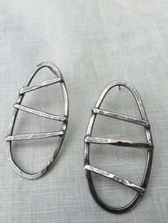 These earrings are forged from sterling silver and are oxidised for a dark finish. They look amazing on.Theyre light weight but have a bold prescence. They are post earrings, measuring 1 1/4 long X 7/8 at the widest part.