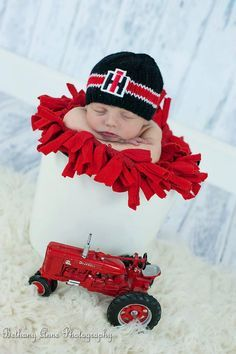 Hand-knit newborn beanie with black/red tractor logo. Please drop me a