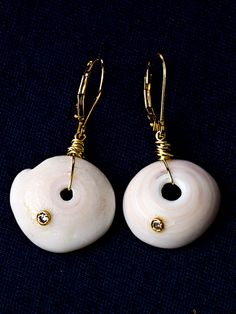 """So cool .. 14K gold and diamond vintage 1960's Hawaiian puka shell drop earrings.  The shells, colors of white, sand and cream tones create the backdrop for the shimmering diamond set into its surface. Incredibly chic for all of those beautiful tunics you have...and anything else you want to pair these organic stunners with. Hangs approximately 1.5"""". One-of-a-kind."""