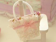 miniatures straw bag coated inside with a cotton cloth with flowers and adorned with a bow to the side.  measure 2 cm in height excluding handle and 3,5 cm in width at the top
