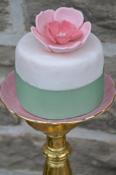 A miniature cake decorated with gum paste dogwood flowers perches atop a gold-rimmed vintage plate.