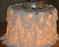 Christmas lights under a table with a white table cloth. This would be super cute for a cake table or sweetheart table if you are doing one