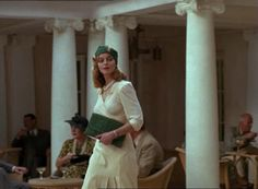White Mischief (1987) - Greta Scacchi as Lady Diana Broughton wearing a white long-sleeved dress with draped bodice and pleated skirt. The accessories include a green clutch bag and matching turban pearl diamond and gold jewellery.  The costumes were designed by Marit Allen.