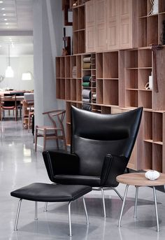Carl Hansen & Søn Flagship Store in Copenhagen. Wegner´s classic, The CH445 Wing Chair with Mogens Koch´s iconic Bookcase system in the background.