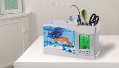 LCD Fish Tank Aquarium - 2 Colours Bring some maritime flair to your work station with the LCD Fish Tank Aquarium      Features overheard LED light and underwater multi-coloured LEDs      Includes decorative pebbles, artificial plant and USB connector      6 nature sound modes create a relaxing ambience – whilst indoors.      Backlit LCD screen displays time, date, alarm clock and...