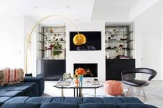 Black glass shelving, gold tall lamp, black chair, orange cushion, blue couch
