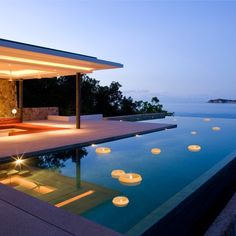Infinity pool with floating candles and living space.