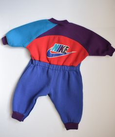 Vintage Nike one-piece, color blocked sweatsuit for baby from 1980s. Purple, teal, blue and red color scheme. Snaps inside legs for easy on and off. Elastic at waist.  Very good vintage condition. Minor sign of wash and wear, including minor piling. No staining.  Tag size 6 months. Modern size estimate 6-12 months. Please refer to following measurements to ensure proper fit. Measurements taken on garment laying flat. Length (shoulder to hem) 22.75 Shoulder to saddle 13.75 Chest (armpit to…