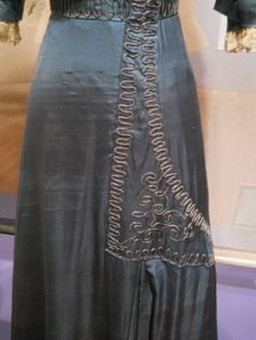 """""""This stunning cornflower blue silk dress features a square neckline which is filled in with netting lace.  The assymetrical details show a definite departure from the more centered and predictable trimming patterns I've seen on many dresses from a decade earlier.  Notice the curled blue cording which is hand-stitched over the upper bodice, waistband, and skirt.  Circa 1910"""""""