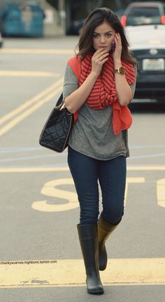 skinnies tucked into rain boots + loose grey oversized tee + red scarf (stripes) + loose hair + structured bag