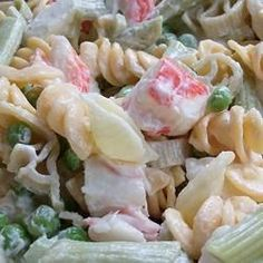 Pretty rainbow pasta is dotted with green peas, crunchy bits of celery and imitation crabmeat, and wrapped in a creamy dressing with a touch of sweetness for a cool, colorful salad.